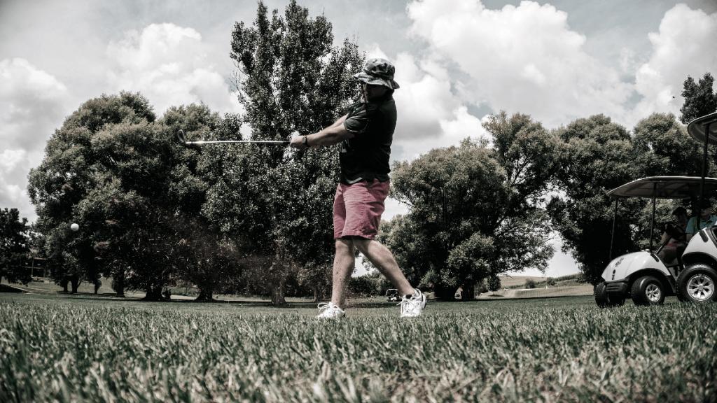 Man Swinging Golf Club wearing Bucket Hat