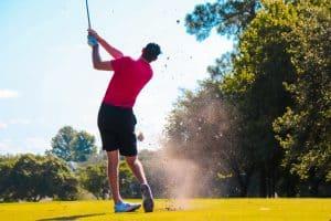 golfer hitting wedge shot on golf course