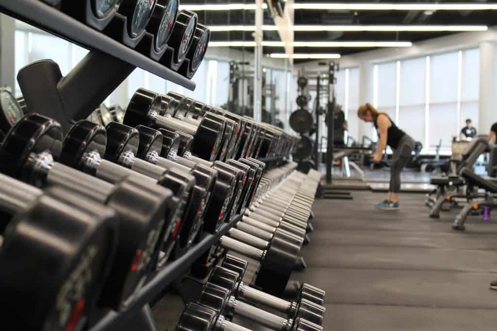 Weight rack in gym with woman exercising in background