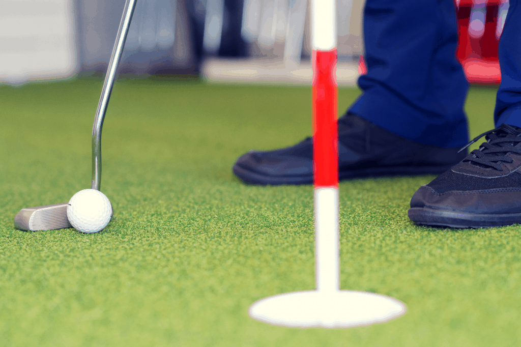 Man putting on indoor putting green