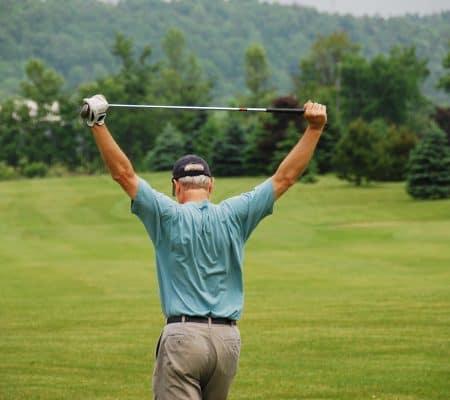 golfer doing standing shoulder stretch