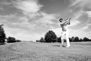 golfer hitting golf ball with driver