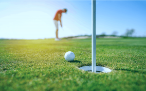 Golfer putting a ball in the hole